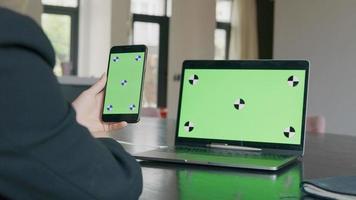 celular com tela verde na mão esquerda na frente da mulher negra, laptop no fundo com tela verde