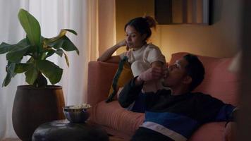 jovem asiático e uma jovem negra assistindo televisão na sala de estar, comendo pipoca