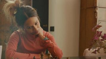 jovem negra olha nervosa ao tabuleiro de xadrez