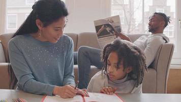 mujer y niña sentada en el suelo a la mesa. libro delante de ellos. mujer habla, mientras escribe en el libro. ella mira a la niña, habla, la niña mira a la mujer, la niña habla. el hombre en el sofá en segundo plano, lee el periódico, mira a la niña, una vez.