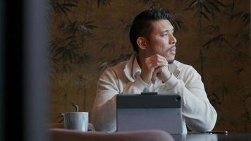 giovane asiatico con il laptop, guardando contemplativamente, lavorando sul suo laptop, prendendo la sua penna