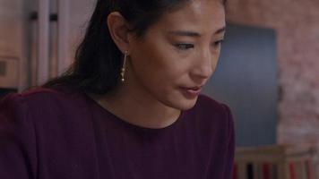 Mujer asiática madura se sienta a la mesa, escribiendo en un cuaderno