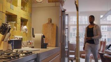 homem maduro entra na cozinha com a xícara na máquina de café, prepara a máquina, espera pelo café video