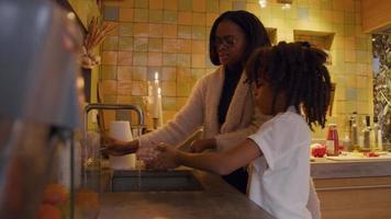 Frau steht vor dem Waschbecken, neben dem Mädchen, wäscht sich gründlich die Hände, Frau spricht, gibt Mädchen Anweisungen, spült Seife ab und schüttelt nasse Hände über dem Waschbecken