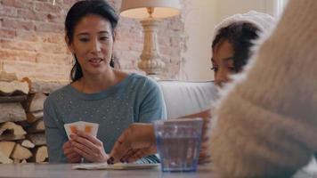 duas mulheres e uma menina sentada à mesa, jogando cartas. mulher observa cartões sendo empilhados por uma garota e outra mulher.