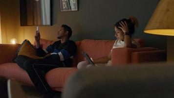 jovem asiático e negra jovem sentada no sofá. homem aperta o controle remoto da mulher segurando o tablet na frente dela