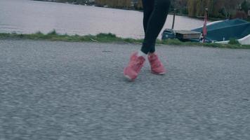 Las piernas y los pies de la joven negra en el parque, moviéndose hacia los lados
