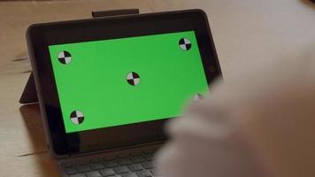 Cerca de las manos del hombre maduro, escribiendo en la computadora portátil, la mano se mueve y escribe nuevamente. portátil en la mesa muestra pantalla verde video