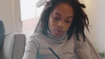 garota se senta à mesa, conversando, observando seu livro de trabalho enquanto escreve nele video