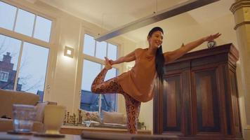 La mujer asiática practica la pose del señor de la danza, yoga, mientras encuentra el equilibrio sobre una pierna, habla y ríe. video