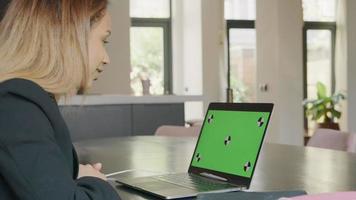 mujer joven negra con portátil con pantalla verde.