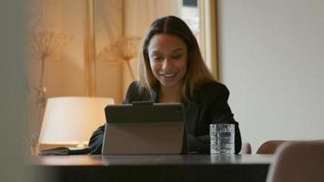jovem empresária negra sentada à mesa, tendo uma videochamada alegre video