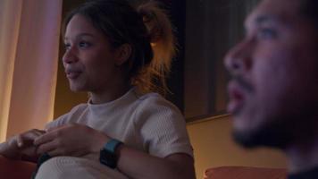 schwarze junge frau und asiatischer junger mann beim fernsehen, frau redet, nimmt popcorn, mann redet, isst popcorn video
