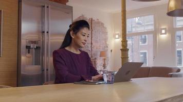 mulher asiática madura se senta à mesa na cozinha, enquanto digita no laptop video