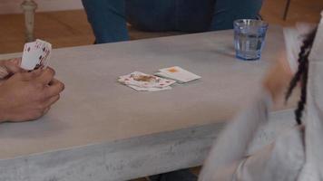 Mesa baja con dos pilas de cartas, manos de niña y mujer y dorso de niña. la niña apunta al hombre, la mano del hombre toma la tarjeta, la mano de la niña pone la tarjeta en la pila. el hombre mira a las mujeres y las niñas. video