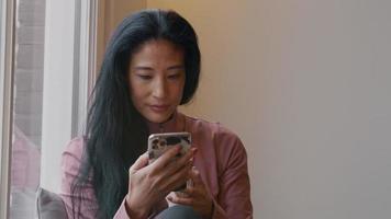 mulher madura sentada no parapeito da janela, olhando e tocando o telefone celular, enquanto toma goles do copo video
