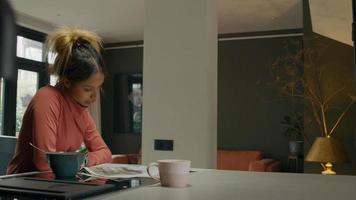 schwarze junge Frau liest Zeitung, sitzt an der Küchentheke, asiatischer junger Mann schließt sich Tablette an, spricht mit Frau, Frau schaut auf Smartwatch