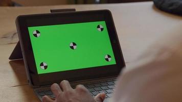 close-up das mãos de homem maduro, digitando no teclado do laptop. laptop na mesa, mostrando tela verde video