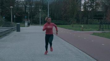 Black young woman in park, doing physical exercise, running fast video