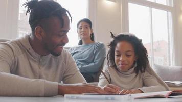 man och flicka sitter på golvet vid bordet och har konversation, medan flickan skriver i arbetsboken. mannen fokuserade på hennes bok. flickan ler, tittar på mannen. kvinna på soffan i bakgrunden. video