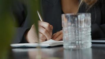 jovem empresária negra sentada à mesa, fazendo anotações com caneta, virando o rosto, olhando contemplativamente video
