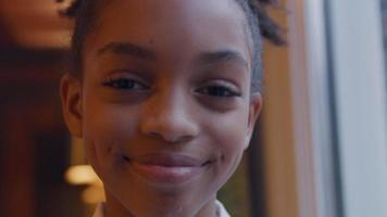 Close up of black girl, looking into camera, smiling, laughing video