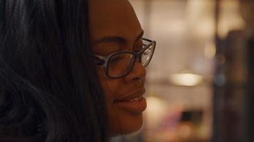 närbild på kvinna med glasögon, talar levande, ler, tittar ner, rynkar pannan på ögonbrynen video
