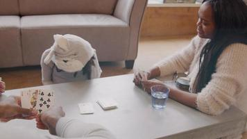 duas mulheres, um homem e uma menina sentados ao redor da mesa, jogando cartas. a menina ergue os olhos, para o homem, ri, olha as cartas dela, a mulher tira a carta da pilha, a garota fala e pretende tirar uma das cartas dela. outra mulher assiste.