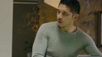 Aziatische jongeman, tikt op het scherm van het apparaat, draait zijn gezicht naar links en naar achteren