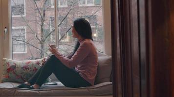 mulher madura sentada no parapeito da janela, olhando pela janela, rindo e conversando, segurando o copo na mão sobre os joelhos dobrados e bebendo video