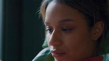 close-up de uma jovem negra, segurando o celular na frente do rosto, colocando o cabelo atrás da orelha video