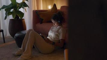 Joven negra sentada sobre una alfombra, con auriculares, relojes de tableta, la cabeza y el pie se mueven ligeramente moviéndose video