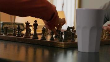 close-up do tabuleiro de xadrez, mãos de uma jovem negra e um jovem asiático jogando xadrez video