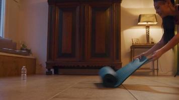 Mujer asiática desenrolla estera de yoga en el suelo y se sienta en posición de loto