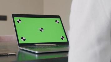 Portátil abierto, con pantalla verde y lápiz en el teclado, brazo borroso