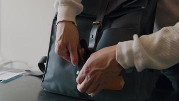 asiatischer junger Mann schließt Rucksack, schaut auf Smartwatch, setzt Gesichtsmaske auf video