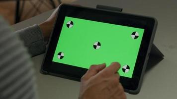 dedo do jovem asiático se movendo e apontando para a tela verde do tablet.