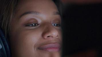 primer plano, de, negro, mujer joven, con, auricular, mirar, dispositivo, sonriente video