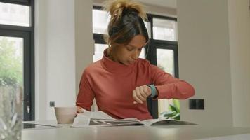 mujer joven negra lee el periódico, mira el reloj inteligente, tocándolo video