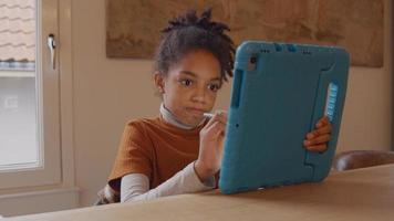 La niña se sienta a la mesa, sostiene la tableta con una mano frente a ella, el lápiz óptico en la otra mano hace líneas y arañazos en la pantalla video