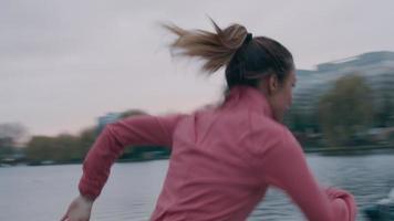 jovem negra no parque, fazendo exercícios físicos, correndo calmamente, sorrindo, fugindo