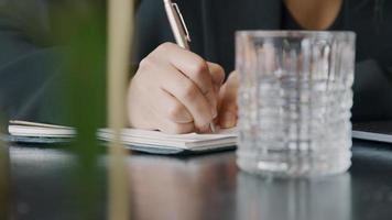 La main droite de la jeune femme noire écrit des notes, avec un stylo, gros plan