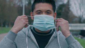 close-up de um jovem asiático parado do lado de fora, colocando uma máscara no rosto, indo embora video