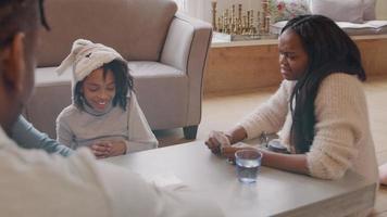 dos mujeres, un hombre y una niña sentados alrededor de la mesa, jugando a las cartas. la niña se ríe y recibe tres cartas. la mujer habla y apunta a las cartas. video