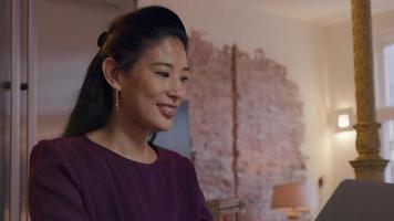mulher asiática madura se senta à mesa na cozinha, assistindo a tela do laptop, sorrindo, digitando, colocando a mão sob o queixo video