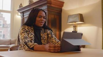kvinnan sitter i vardagsrummet vid bordet, bärbar dator framför henne, samtidigt som hon har videosamtal. hon pratar, tar på sig glasögonen, sätter upp tummen, pratar, nickar, skrattar video