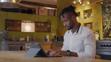 homem maduro se senta à mesa da cozinha, digitando em seu laptop, assiste no smartphone, tocando nele video