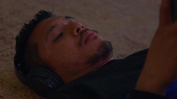 close-up de jovem asiático, deitado no chão, fone de ouvido nas orelhas video