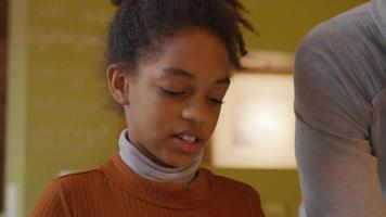 garota olha para baixo enquanto fala com o homem ao lado dela. parte do rosto, ombro e braço do homem mostrado video