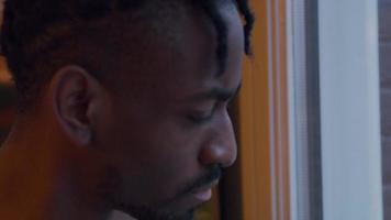 Close up of black man looking through window tout en mettant le masque facial, en l'ajustant video